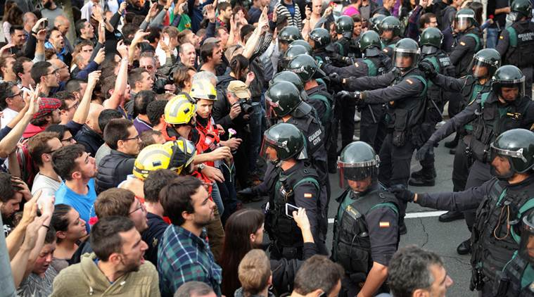 People face off with Spanish Civil Guard officers outside a polling station for the banned independence referendum in Sant Julia de Ramis